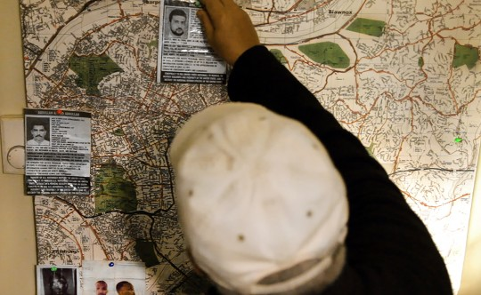 """FBI Informant """"Shariff"""" pins photographs of the FBI's most wanted terrorists to an operational map of Pitssburgh, Pennsylvania.  2012."""