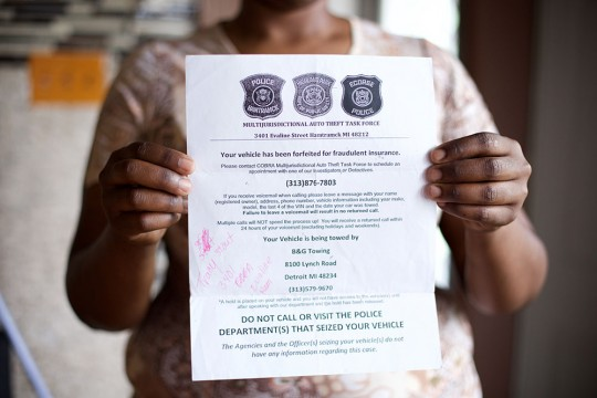 """Tracy Martin, 36, of Detroit  holding a flier by Highland Park police who had towed her truck, saying """"Multi Jurisdictional Auto Theft Task Force."""" Sunday, May 17, 2015 in Detroit, Michigan."""