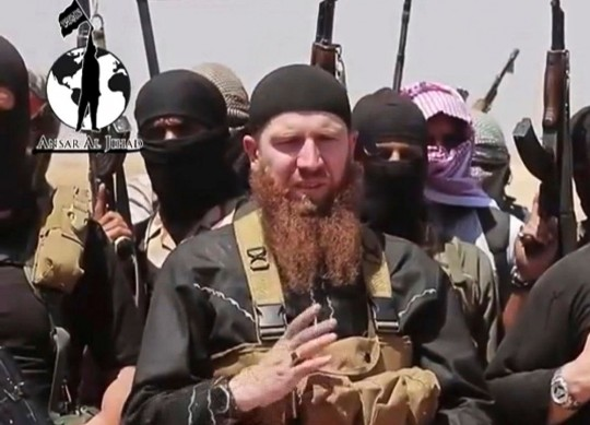 This image made from undated video posted during the weekend of June 28, 2014 on a social media account frequently used for communications by the Islamic State of Iraq and the Levant (ISIL), which has been verified and is consistent with other AP reporting, shows Omar al-Shishani standing next to the group's spokesman among a group of fighters as they declare the elimination of the border between Iraq and Syria. Al-Shishani, one of hundreds of Chechens who have been among the toughest jihadi fighters in Syria, has emerged as the face of the Islamic State of Iraq and the Levant, appearing frequently in its online videos — in contrast to the group's Iraqi leader, Abu Bakr al-Baghdadi, who remains deep in hiding and has hardly ever been photographed. (AP Photo/militant social media account via AP video)