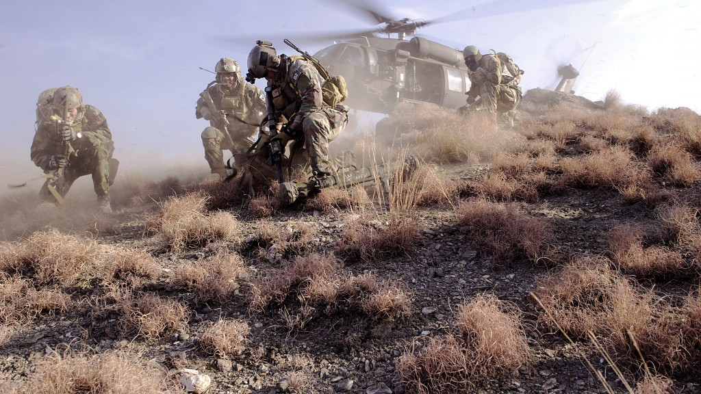 U.S. Special Operations personnel take cover to avoid flying debris as they prepare to board a UH-60 Black Hawk helicopter during a mission in Kunar province, Afghanistan, Feb. 25, 2012. The Soldiers were conducting reconnaissance for a future village stability platform, a site Afghan forces and coalition Special Operations Forces will use to live and work with villagers. (DoD photo by Mass Communication Specialist 2nd Class Clayton Weiss, U.S. Navy/Released)