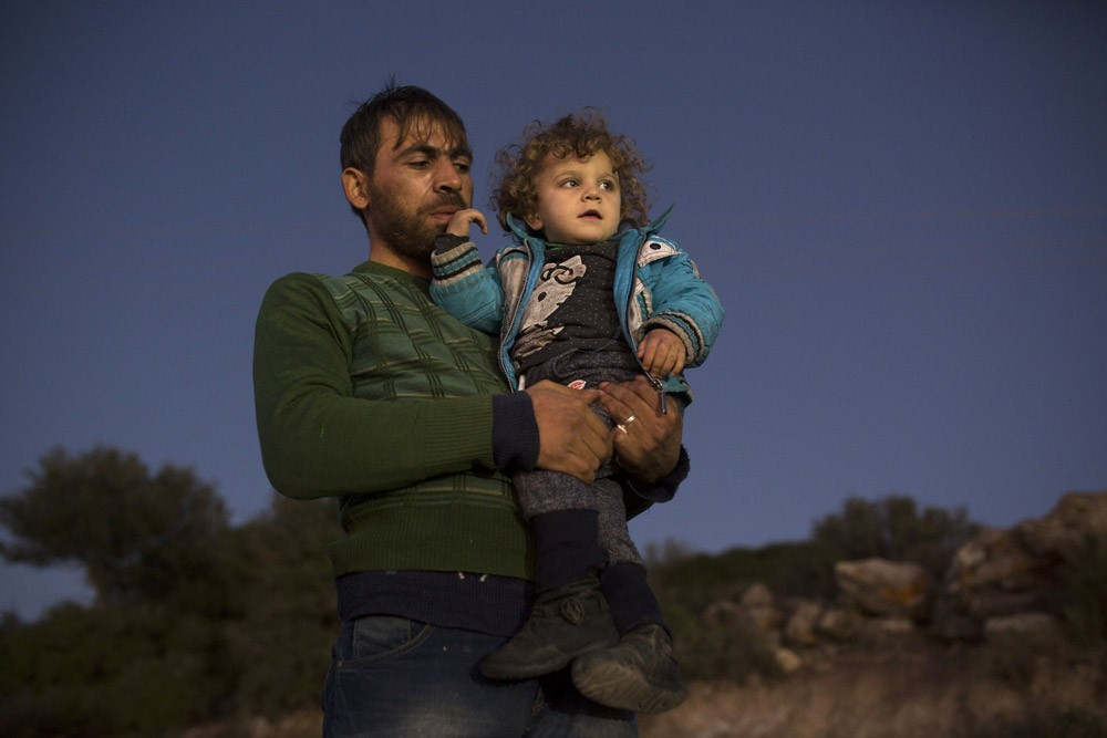 Syrian refugee Ammar Alewi with his two year -old Fatma as he waits near the Oxy Camp for a bus to take them to another  camp for processing on  November 11 ,2015. Earlier in the day , Ammar crossed  the  Aegean Sea from Turkey  on an overcrowded rubber dinghy boat leaving his wife  and baby , still in Aleppo, Syria . They  hope to join them once he hopefully arrives with his daughter to  Germany .(Photo by Heidi Levine/Sipa Press).