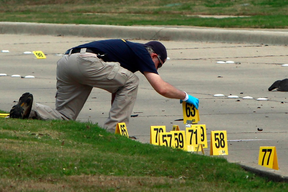 "GARLAND, TX - MAY 4: A member of the FBI Evidence Response Team investigates the crime scene outside of the Curtis Culwell Center after a shooting occurred the day before, on May 04, 2015 in Garland, Texas. During the ""Muhammad Art Exhibit and Cartoon Contest,"" on May 03, Elton Simpson of Phoenix, Arizonia and Nadir Soofi opened fire, wounding a security guard. Police officers shot and killed Simpson at the scene. The provocative cartoon event was billed by organizers as a free speech event while critics deemed it to be anti-Islamic.  (Photo by Ben Torres/Getty Images)"