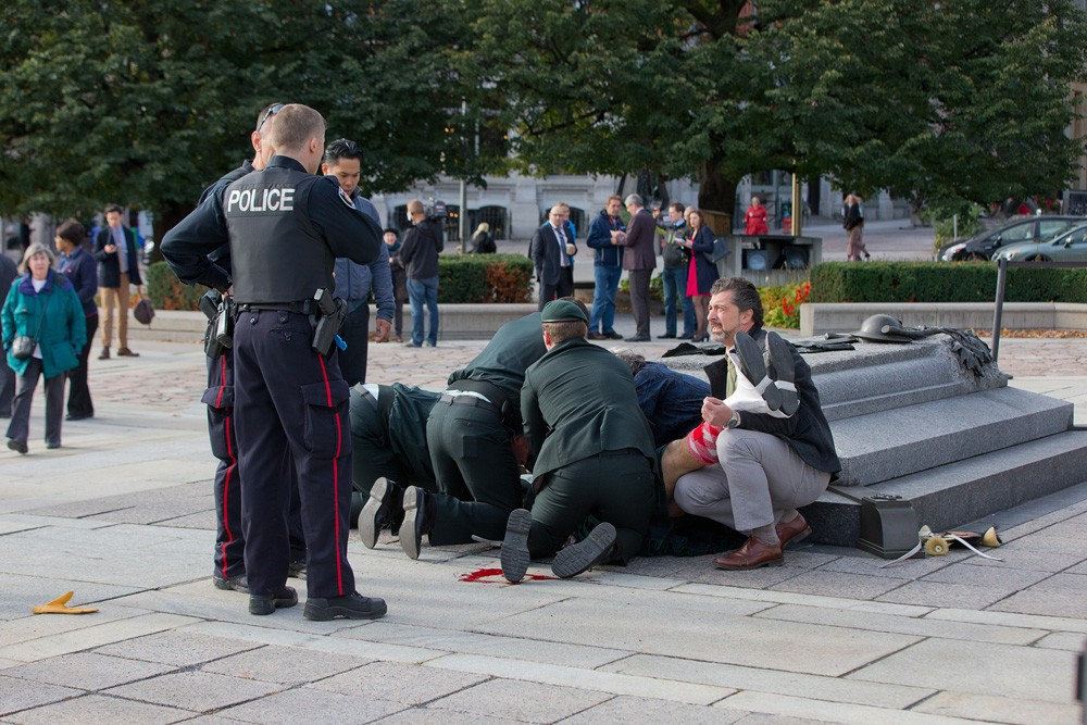 Image #: 32693473    OTTAWA, CANADA - OCTOBER 22: Police, bystanders and soldiers aid a fallen soldier at the War Memorial as police respond to an apparent terrorist attack  on October 22, 2014 in Ottawa, Canada.  A GUNMAN is believed to have shot a soldier as he was standing guard at the National War Memorial in Ottawa, Canada, this morning (Wednesday, October 22). It is believed police then chased the man into the main parliament building at Parliament Hill, where more shots were fired. Police are hunting the streets and buildings for further suspects and have asked the public to stay away from the area. There is also a report of shootings at the Rideau Centre mall in downtown, a short distance from the War Memorial. The wounded soldier was taken into an ambulance and treated by medical personnel and is condition is unclear. The incident comes after Canada raised its terror threat level from low to medium after a Muslim convert deliberately ran over two soldiers, killing one of them.     Wayne Cuddington/Barcroft Media /Landov