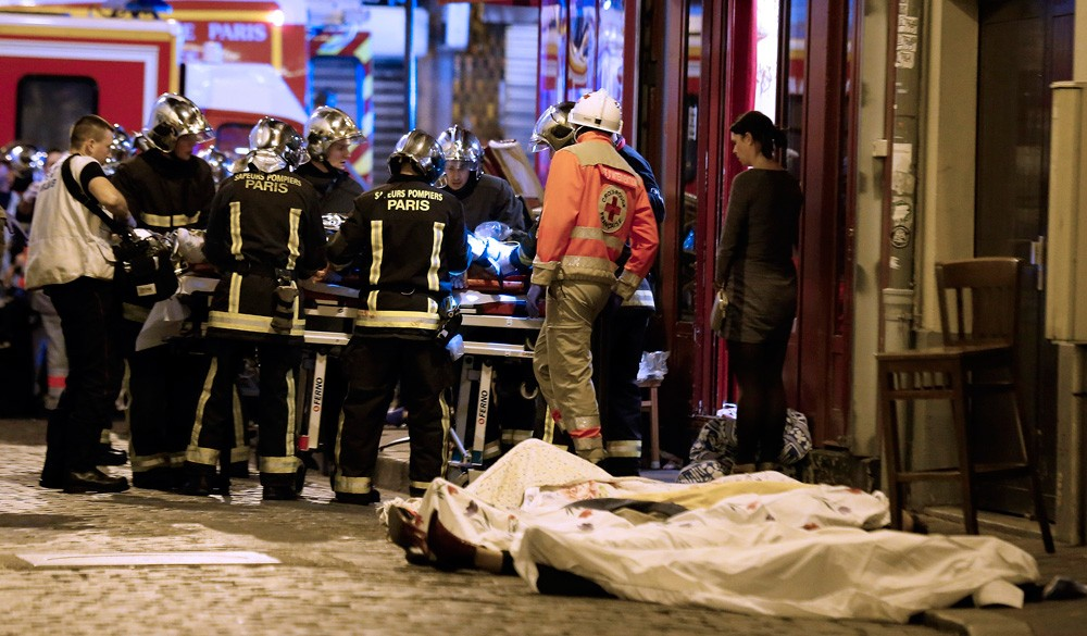 Rescue workers gather at victims in the 10th district of Paris, Friday, Nov. 13, 2015. Several dozen people were killed in a series of unprecedented attacks around Paris on Friday, French President Francois Hollande said, announcing that he was closing the country's borders and declaring a state of emergency. (AP Photo/Jacques Brinon)