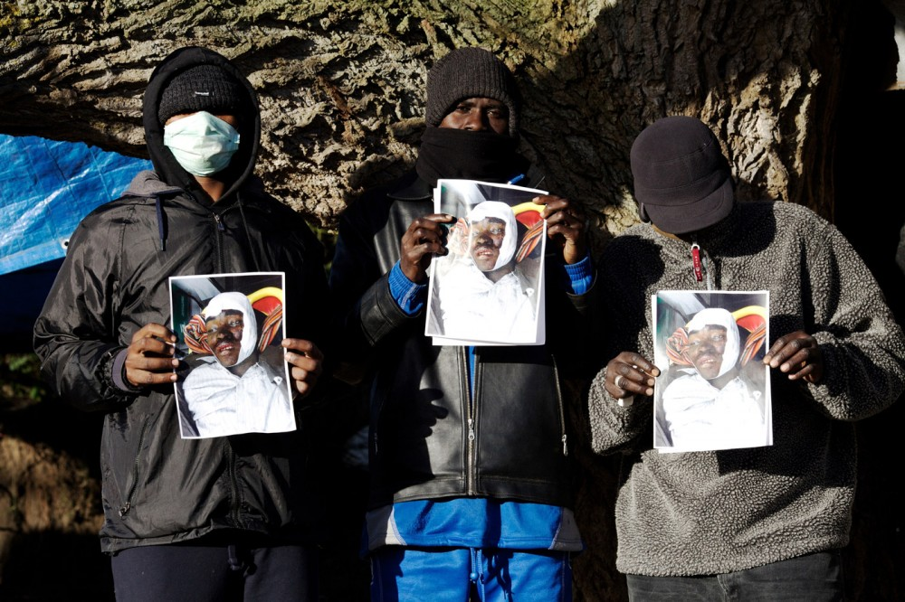 "Friends hold a photograph of Yousef (last name unknown) who was killed 03 December 2015 near the refugee camp known as ""The Jungle"" in Calais, France. He is the 18th refugee to die since June 2015 trying to get into the tunnel that connects France to the United Kingdom, and it is alleged by eyewitnesses that he was run down on purpose by a van driver. (John D McHugh/Verifeye Media)"