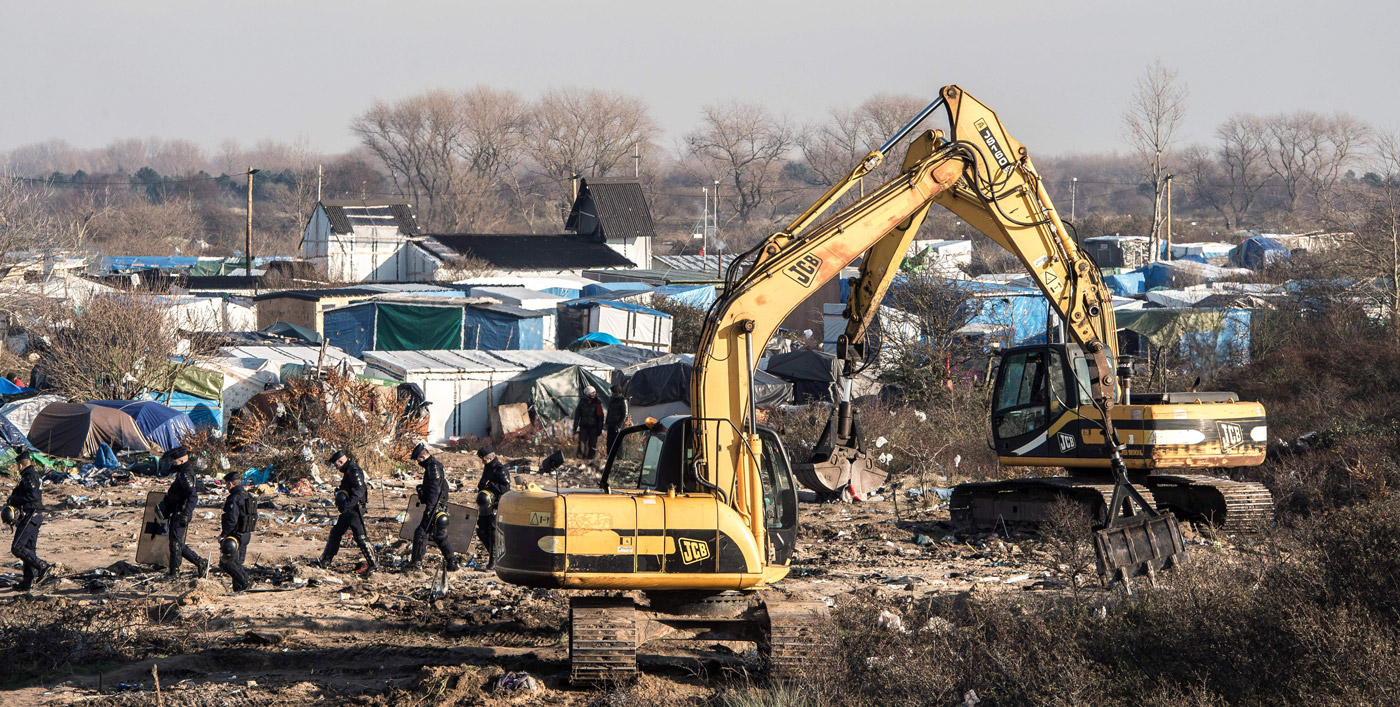 "Workers use excavators on January 20, 2016, to clear a zone where makeshift shelters were set up in the migrant shantytown on the outskirts of Calais known as the ""Jungle""(Photo credit should read PHILIPPE HUGUEN/AFP/Getty Images)"