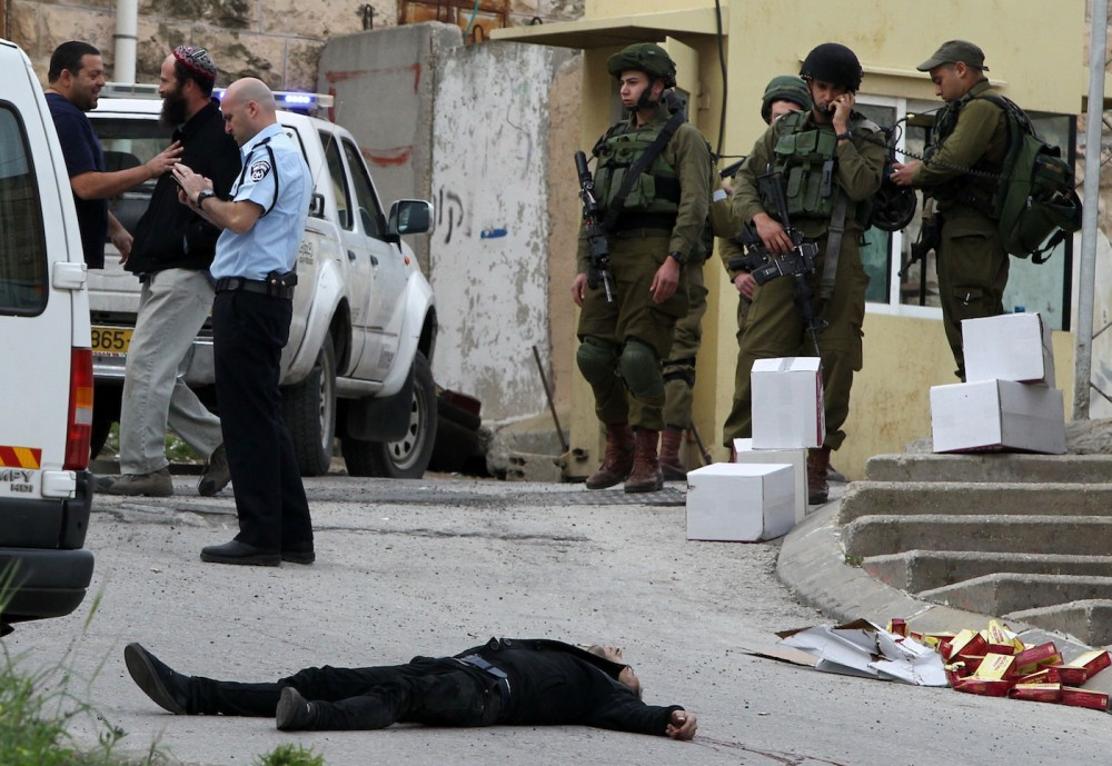 EDITORS NOTE: Graphic content / Israeli soldiers and police surround the body of one of two Palestinians who were killed after wounding an Israeli soldier in a knife attack before being shot dead by troops, an army spokeswoman said, at the entrance to the heavily guarded Jewish settler enclave of Tal Rumeda in the city centre of the West Bank town of Hebron on March 24, 2016.An Israeli soldier was detained after allegedly shooting a wounded Palestinian assailant in the head and killing him as he lay on the ground, the army said. In the video released by B'Tselem, an Israeli rights non-governmental organisation, the soldier appears to shoot the Palestinian again in the head without provocation as he lay wounded from a gun shot wound on the ground. / AFP / HAZEM BADER (Photo credit should read HAZEM BADER/AFP/Getty Images)