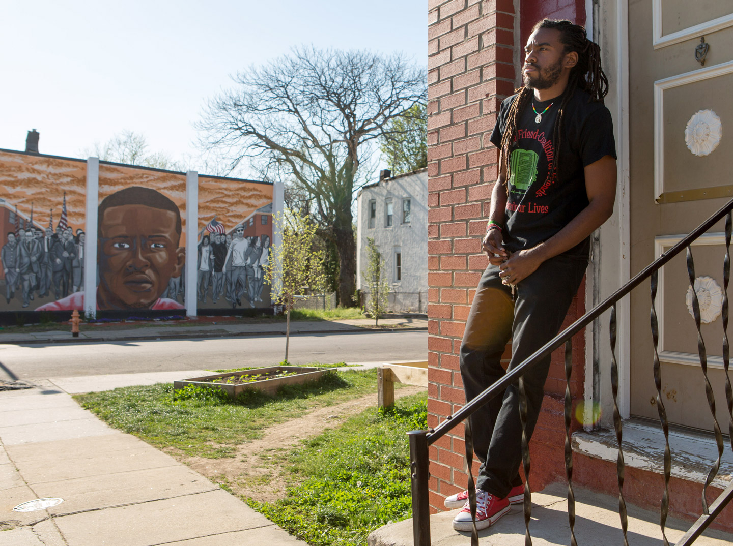 Attorney and activist Taalib Saber poses for a photo outside a house that is across the street from where Freddie Gray, who died while in police custody just over one year ago, was picked up by police in Baltimore, Maryland, April 23, 2016. Saber is using the home, which he found vacant, for children's community activities. (photo by Allison Shelley)