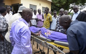 Relatives and other mourners watch as the body of South Sudanese journalist Peter Julius Moi is taken into the mortuary in Juba, South Sudan Thursday, Aug. 20, 2015. The father of Moi, a reporter for the Corporate Weekly, says unknown gunmen shot his son twice in the back and killed him late Wednesday, Aug. 19, 2015 on the outskirts of the capital Juba, in an attack that came days after President Salva Kiir was reported to have threatened to kill reporters