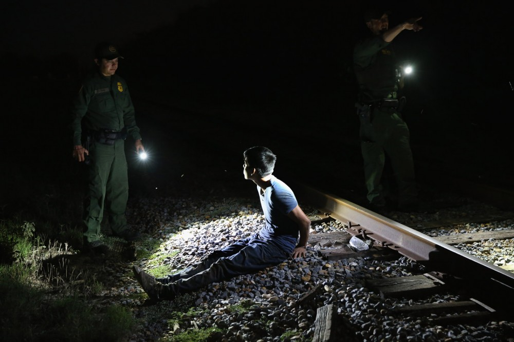 MCALLEN, TX - SEPTEMBER 08:  U.S. Border Patrol agents detain an undocumented immigrant along a railroad track near the Rio Grande River at the U.S.-Mexico border on September 8, 2014 near McAllen, Texas. Thousands of undocumented immigrants continue to cross illegally into the United States, although the numbers are down from a springtime high. Texas' Rio Grande Valley area is the busiest sector for illegal border crossings, especially for Central Americans, into the U.S.  (Photo by John Moore/Getty Images)