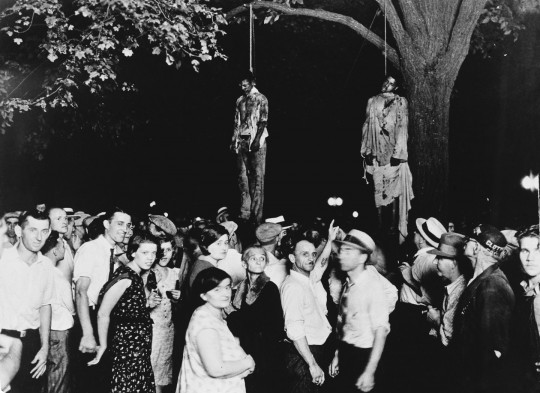A crowd gathering to witness the killing of Thomas Shipp and Abram Smith, two victims of lynch law in Marion, Indiana, 7th August 1930. This image was the inspiration for the poem 'Strange Fruit' by Abel Meeropol.  (Photo Lawrence Beitler/by Hulton Archive/Getty Images)