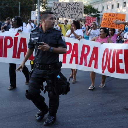 "Demonstrators hold a banner reading ""Olympics for whom?"" next to a policeman during a protest against the Rio 2016 Olympic Games in Rio de Janeiro, Brazil on August 5, 2015.       AFP PHOTO / TASSO MARCELO        (Photo credit should read TASSO MARCELO/AFP/Getty Images)"