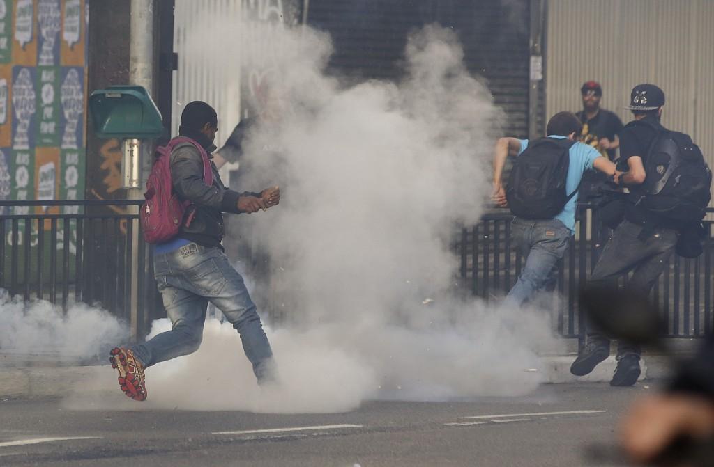 Los manifestantes corren en medio de una nube de gas lacrimógeno durante una protesta organizada por el Movimiento de los Trabajadores Sin Techo, en Sao Paulo, Brasil, miércoles, 1 de junio de 2016. El movimiento organizó la protesta contra el presidente en funciones, Michel Temer y en apoyo del presidente suspendido, Dilma Rousseff.  (Foto AP / Andre Penner)