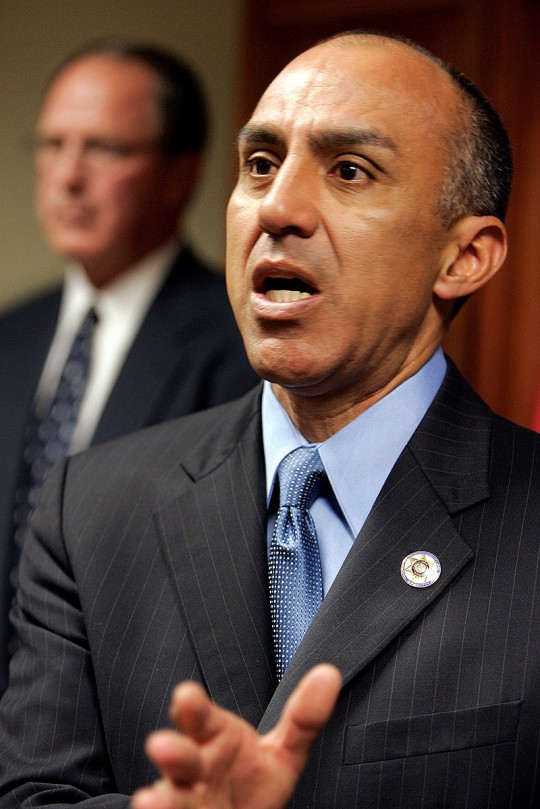 Michael Ramos, San Bernardino County District Attorney, speaks during a news conference as the county sheriff Gary Penrod listens in the background Tuesday, March 7, 2006, in San Bernardino, Calif. Ramos announced that his office filed a charge of Attempted Voluntary Manslaughter against San Bernardino County Sheriff's Deputy Ivory Webb in the shooting of Elio Carrion.   (AP Photo/Ric Francis)