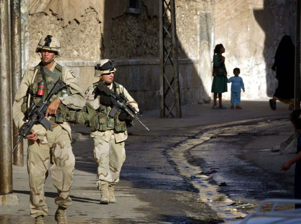 ** FILE ** Soldiers of the 101st Airborne Division patrol a street in Mosul, 400 kms (250 miles) north of Baghdad in this Sept. 13, 2003 file photo.  The Army is spread so thin around the globe by war and the threat of war that in planning for another rotation of combat troops into Iraq as early as this fall, it had little choice but to call on the same soldiers who led the charge into Baghdad last spring.  (AP Photo/Misha Japaridze, File)