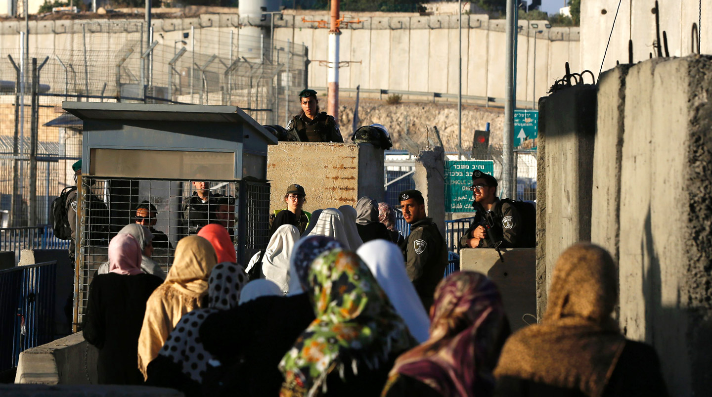 Palestinian women wait to cross through the Qalandia checkpoint near the West Bank city of Ramallah on June 10, 2016, as they head to Jerusalem's Al-Aqsa mosque for the first Friday prayer of the holy Muslim fasting month of Ramadan.Israeli Prime Minister Benjamin Netanyahu announced a slew of punitive and deterrent measures against Palestinians in the wake of the shooting in a popular Tel Aviv nightspot, the deadliest attack in a months-long wave of violence. Among the measures, the Israeli government said it was revoking entry permits for more than 80,000 Palestinians to visit relatives in Israel during the holy Muslim month of Ramadan, a move likely to further stoke tensions. / AFP / ABBAS MOMANI (Photo credit should read ABBAS MOMANI/AFP/Getty Images)