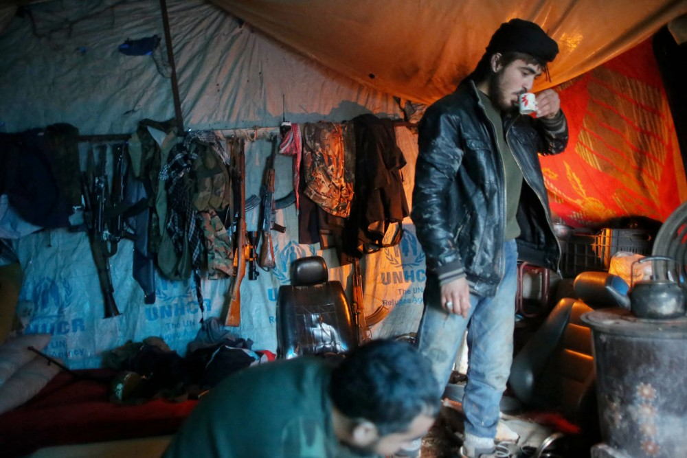 Opposition fighters from the Ahrar al-Sham group drink coffee inside a tent in a rebel-held area of the Handarat region, located just north of the Syrian city of Aleppo, on December 28, 2014, as pro-government forces and rebels continue their fight in the area for control of the main supply route from Turkey. Handarat has been divided since a rebel offensive in summer 2012 between loyalist sectors in the west of the city and insurgent-held territory in the east. AFP PHOTO / AHMED DEEB        (Photo credit should read AHMED DEEB/AFP/Getty Images)