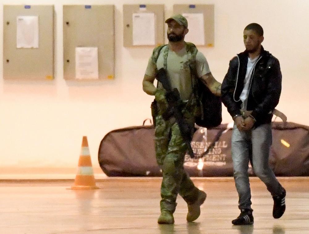 Suposto terrorista é escoltado por policial federalno aeroporto de Brasilia, em 12 de julho de 2016. Autoridades brasileiras prenderam membros de uma supostaorganização terrorista que atacaria durante os Jogos Olímpicos.