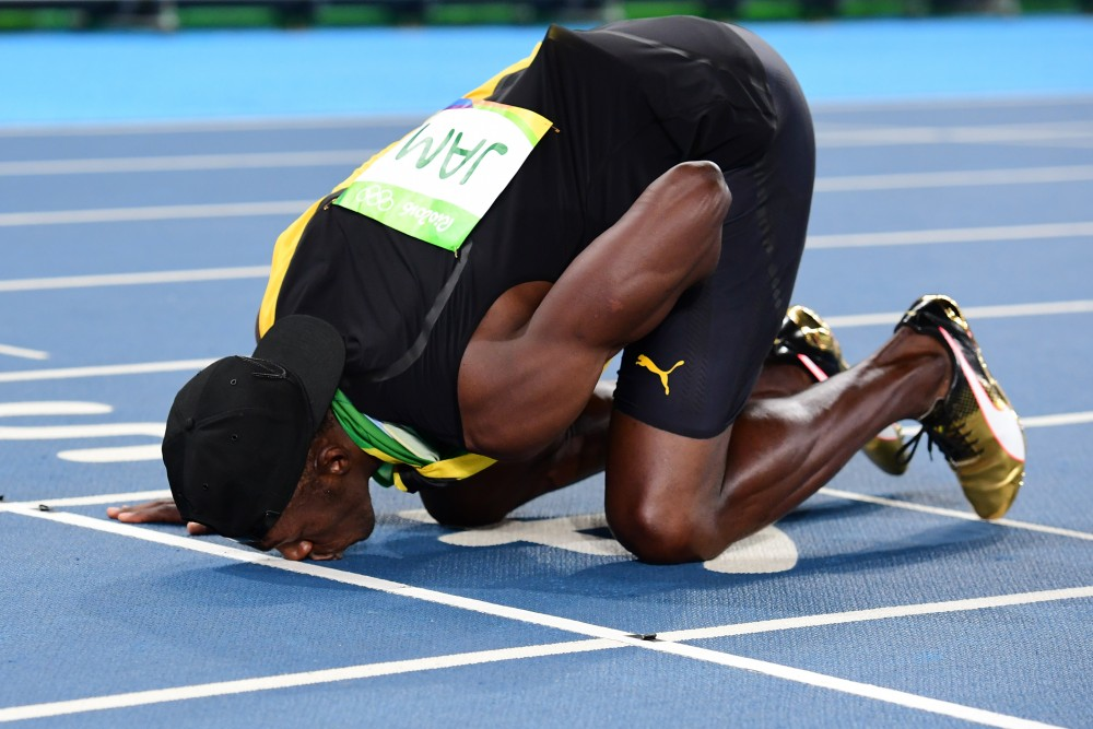 Jamaica's Usain Bolt kisses the track as he celebrates Team Jamaica winning the Men's 4x100m Relay Final during the athletics event at the Rio 2016 Olympic Games at the Olympic Stadium in Rio de Janeiro on August 19, 2016.   / AFP / FRANCK FIFE        (Photo credit should read FRANCK FIFE/AFP/Getty Images)