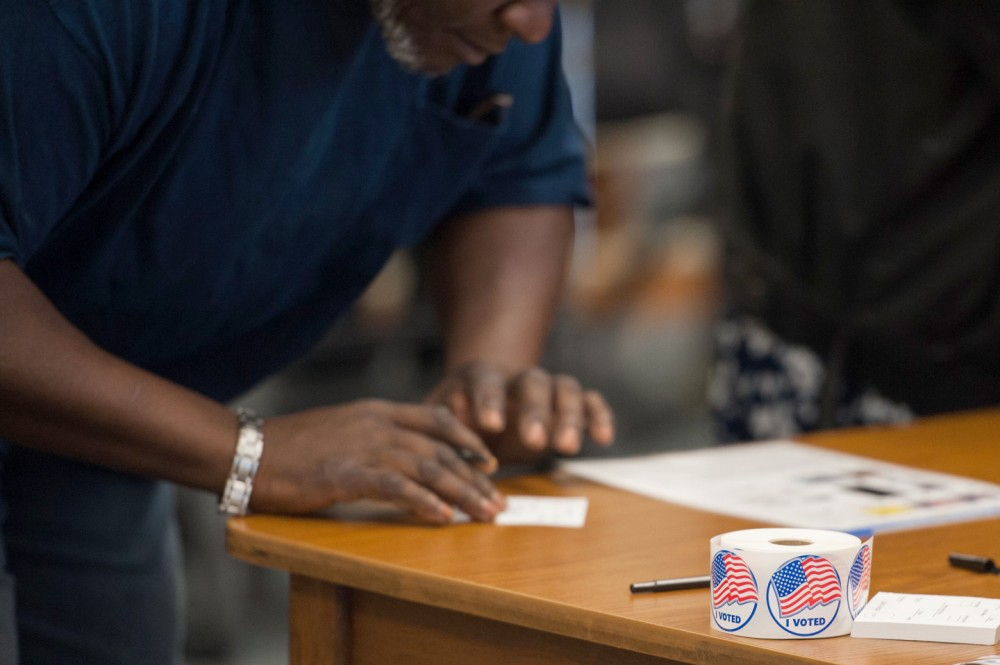 Voting stickers are seen as a man is checked in to receive his ballot during Missouri primary voting at the Griffith Elementary School on March 15, 2016 in Ferguson, Missouri.Voters began going to the polls Tuesday in five make-or-break presidential nominating contests, with Republican Donald Trump and Democrat Hillary Clinton seeking to tighten their grip as their party's front runners. / AFP / Michael B. Thomas (Photo credit should read MICHAEL B. THOMAS/AFP/Getty Images)