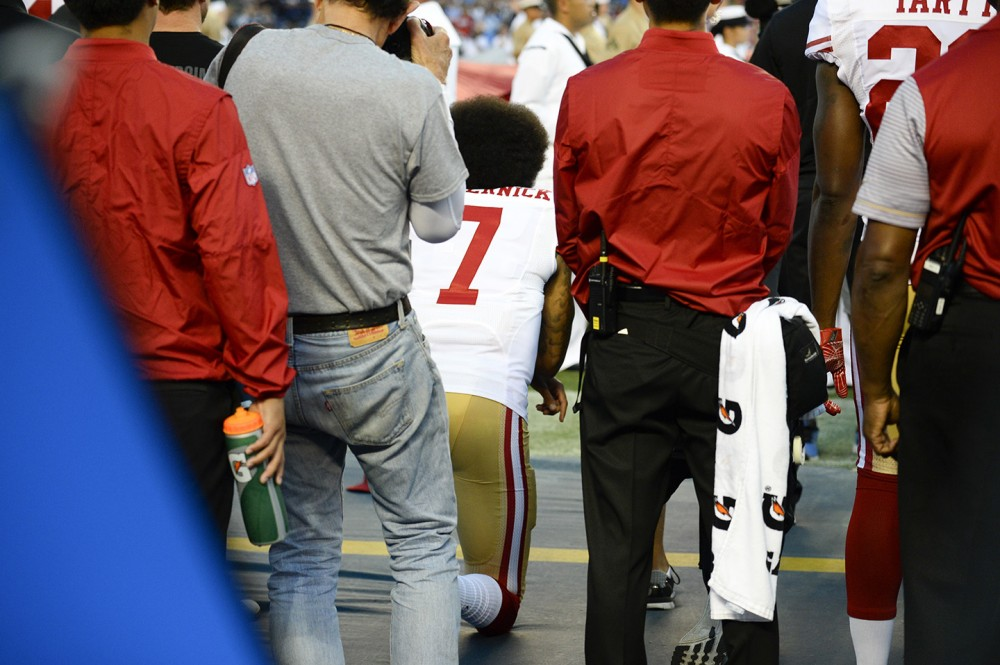 San Francisco 49ers quarterback Colin Kaepernick, middle, kneels during the national anthem before the team's NFL preseason football game against the San Diego Chargers, Thursday, Sept. 1, 2016, in San Diego. (AP Photo/Denis Poroy)