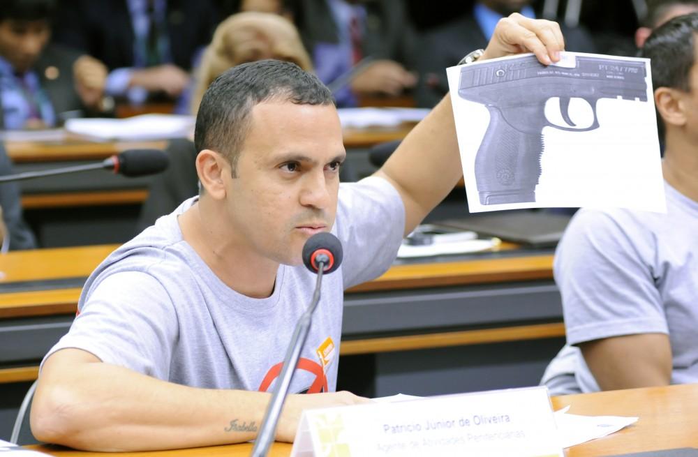 Agente mostra arma com a qual se acidentou, uma PT 24/7, que está proibida de ser comercializada nos EUA, mas é uma das mais usadas pelas PM's do Brasil