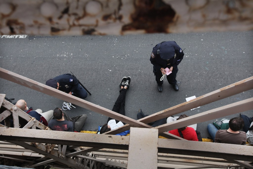 NEW YORK, NY - OCTOBER 01: Police arrest demonstrators affiliated with the Occupy Wall Street movement after they attempted to cross the Brooklyn Bridge on the motorway on October 1, 2011 in New York City. This portion of the bridge is not intended for pedestrians and as the marchers attempted to cross, they were stopped midway by police. Hundreds were arrested. (Photo by Mario Tama/Getty Images)