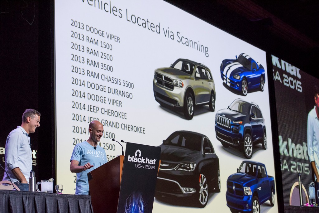Charlie Miller, security researcher for Twitter Inc. and a former NSA hacker, right, speaks as Chris Valasek, director of vehicle security research at the consultancy IOActive, listens during a presentation about a remote exploitation of a passenger vehicle demonstration at the Black Hat Conference in Las Vegas, Nevada, U.S., on Wednesday, Aug. 5, 2015. Features that buyers now expect in most modern automobiles, such as driving directions and restaurant guides, count on a constant connection to a telecommunications network. But that link also makes cars vulnerable to security invasions like those that threaten computers in homes and businesses. Photographer: David Paul Morris/Bloomberg via Getty Images