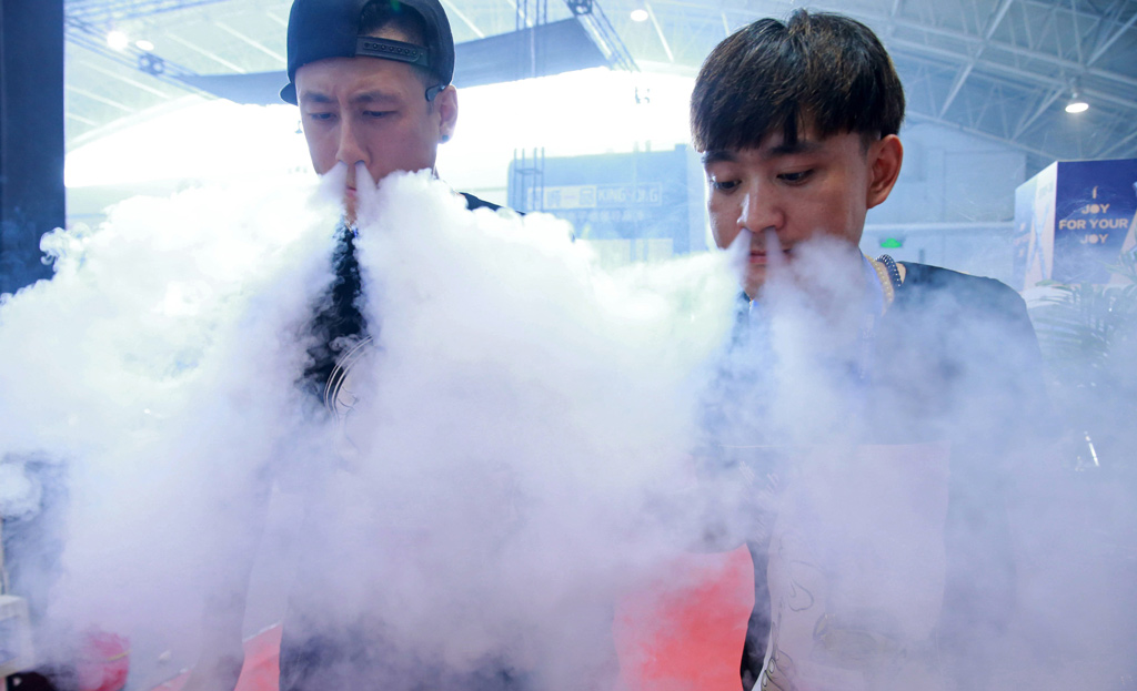 This picture taken on July 23, 2015 shows sales staff exhaling vapour while demonstrating their electronic cigarette products at the Beijing International Vapor Distribution Alliance Expo, or the Vape China Expo, at the China International Exhibition Center in Beijing.  CHINA OUT     AFP PHOTO        (Photo credit should read STR/AFP/Getty Images)