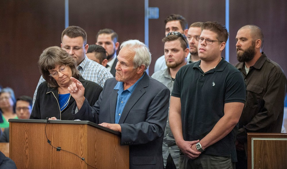 With his wife Raquel Herr by his side at left, Steve Herr, center, father of Samuel Herr, points his finger toward Daniel Wozniak as he speaks in Superior Court, Friday, Sept. 23, 2016 in Santa Ana, Calif. Daniel Patrick Wozniak, who killed Samuel Herr and Julie Kibuishi as part of a plot to steal money to pay for his wedding and honeymoon was sentenced to death Friday. (Mark Rightmire/The Orange County Register via AP)