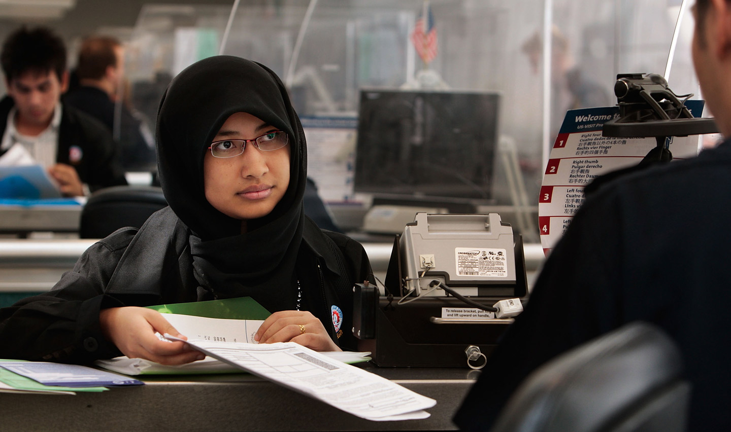 NEWARK, NJ - AUGUST 24:  A woman arriving from overseas gives paperwork to a border control officer  upon arriving into Newark International Airport August 24, 2009 in Newark, New Jersey.   Officials with U.S. Customs and Border Protection are introducing are introducing the Global Entry program, which allows pre-screening and approval of travelers and faster trips through customs and passport lines upon arriving into the United States.  (Photo by Chris Hondros/Getty Images)