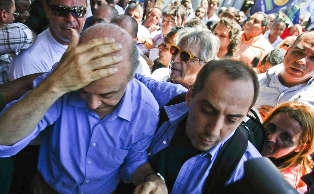 "Brazil's presidential candidate Jose Serra (L) of the Social Democratic Party of Brazil protects his head after being ""knocked silly"" by a thrown object, during a rally in Campo Grande, 55 km from Rio de Janeiro's downtown, on October 20, 2010. Serra and rival Dilma Rousseff of the ruling Workers' Party, will face on October 31 in the run-off election. AFP PHOTO/Cesar Da Silva (Photo credit should read CESAR DA SILVA/AFP/Getty Images)"