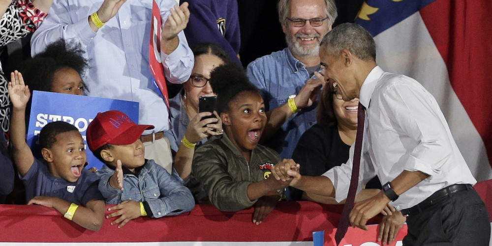 President Barack Obama greets young supporters as he arrives for a campaign rally for Democratic presidential candidate Hillary Clinton in Charlotte, N.C., Friday, Nov. 4, 2016. (AP Photo/Chuck Burton)