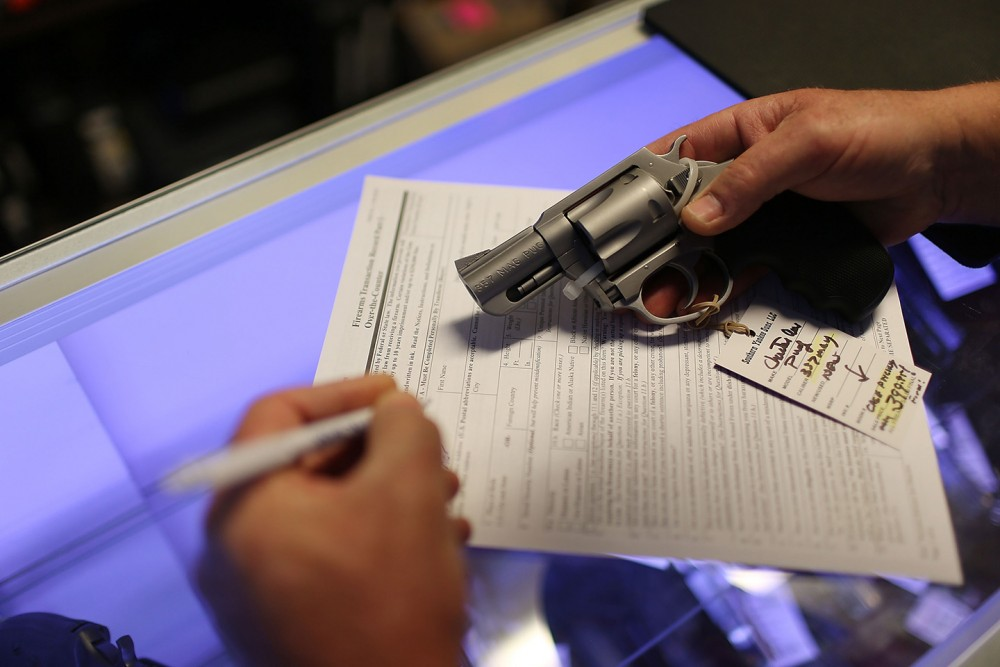 DELRAY BEACH, FL - JANUARY 05:  Mark O'Connor fills out his Federal background check paperwork as he purchases a handgun at the K&W Gunworks store on the day that U.S. President Barack Obama in Washington, DC announced his executive action on guns on January 5, 2016 in Delray Beach, Florida.  President Obama announced several measures that he says are intended to advance his gun safety agenda.  (Photo by Joe Raedle/Getty Images)