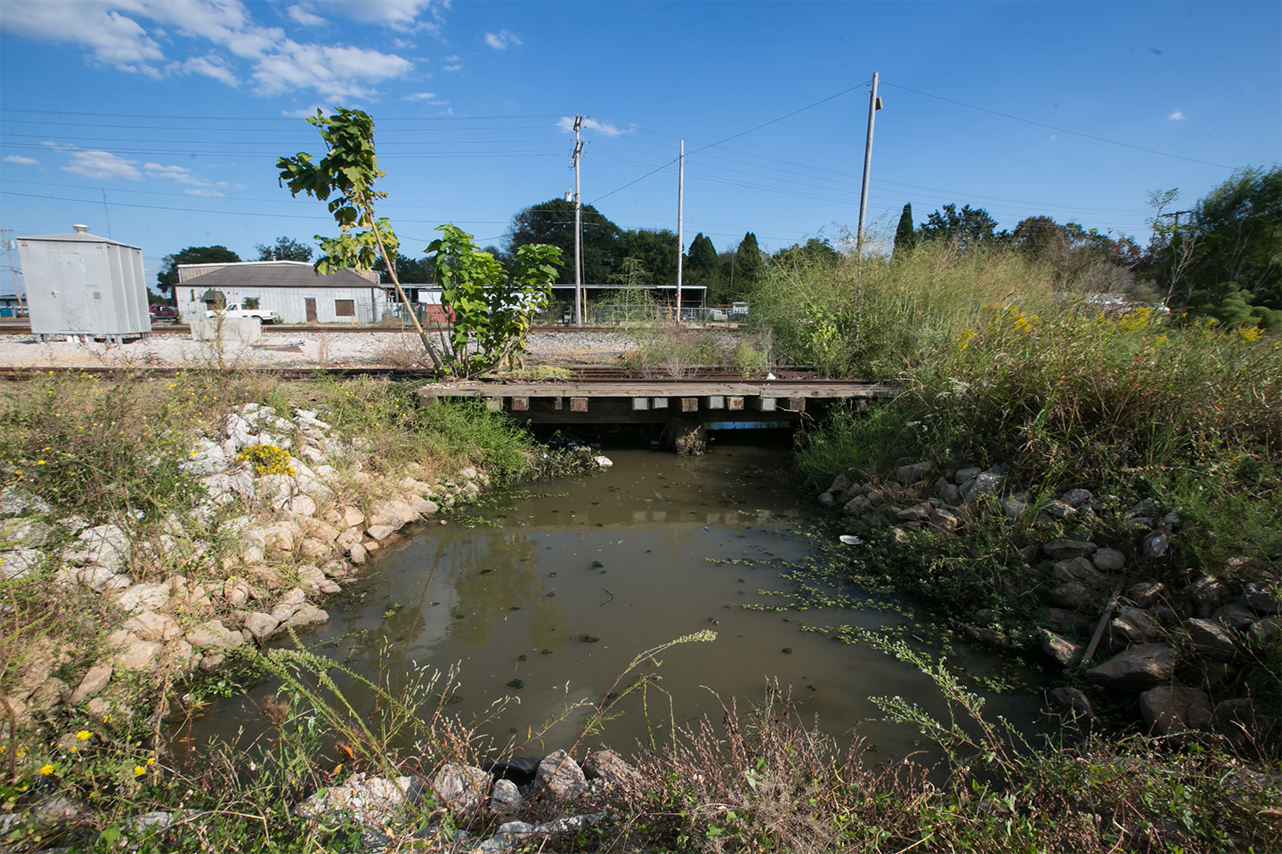 A polluted ditch containing creosote runs along the property of the old Kerr McGee site and 14th Avenue in Columbus, Mississippi.