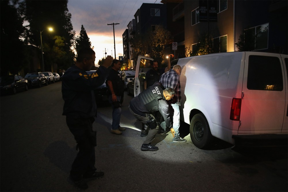 LOS ANGELES, CA - OCTOBER 14:  A man is detained by Immigration and Customs Enforcement (ICE), agents early on October 14, 2015 in Los Angeles, California. ICE agents said the undocumented immigrant was a convicted criminal and gang member who had previously been deported to Mexico and would be again. ICE builds deportation cases against thousands of undocumented immigrants, most of whom, they say, have criminal records. The number of ICE detentions and deportations from California has dropped since the state passed the Trust Act in October 2013, which set limits on California law enforcement cooperation with federal immigration authorities.  (Photo by John Moore/Getty Images)