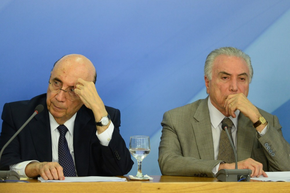 Brazilian President Michel Temer (R) and Finance Minister Henrique Meirelles (L) gesture during the announcement of new measures to stimulate the economy, in the Planalto Palace on December 15, 2016 in Brasilia. / AFP / ANDRESSA ANHOLETE        (Photo credit should read ANDRESSA ANHOLETE/AFP/Getty Images)