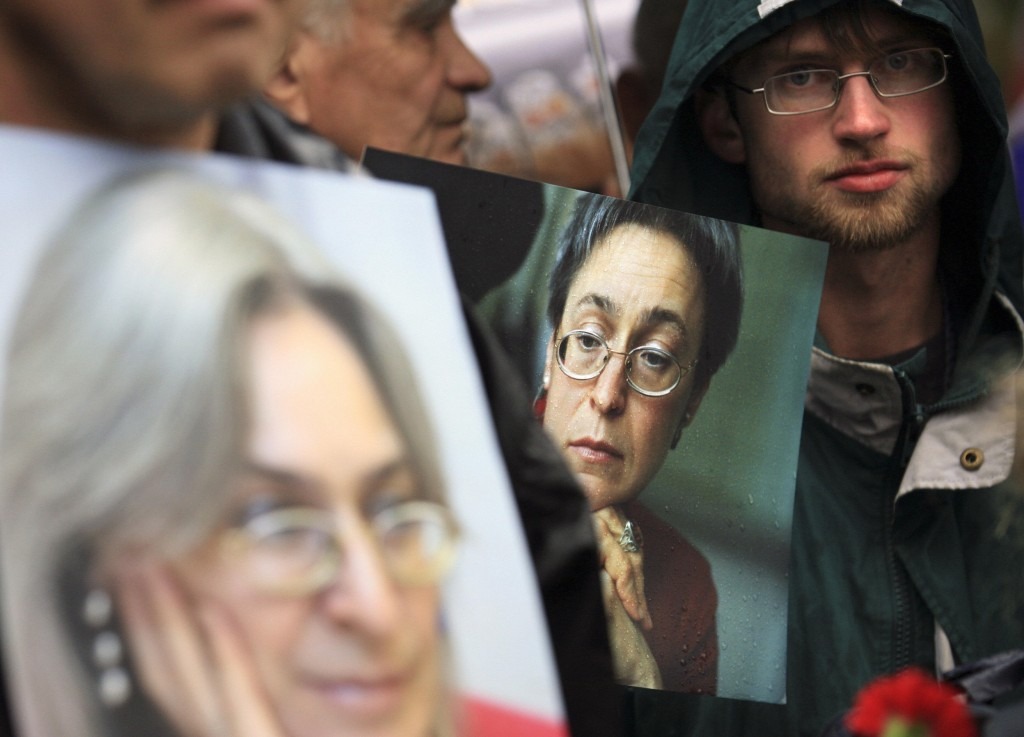 People hold pictures of Russian journalist Anna Politkovskaya during a rally in central Moscow, 07 October 2007. Hundreds of Russian opposition activists rallied in central Moscow under a heavy security presence to mark the anniversary of the killing of investigative journalist Politkovskaya. AFP PHOTO / DMITRY KOSTYUKOV (Photo credit should read DMITRY KOSTYUKOV/AFP/Getty Images)