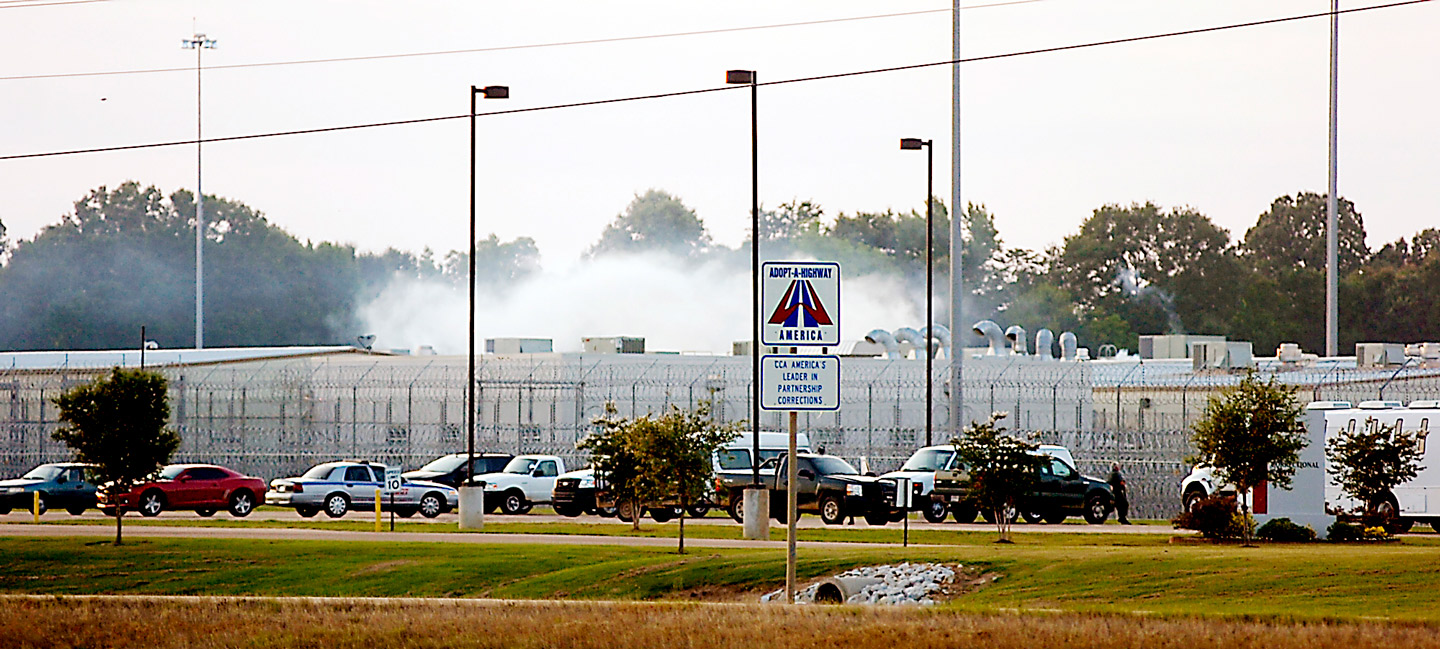 """Smoke rises above the Adams County Correctional Center in Natchez, Miss., Sunday, May 20, 2012, during an inmate disturbance at the prison. A guard at the southwest Mississippi prison died Sunday and several other employees were injured during what the facility's private operator is calling """"an inmate disturbance"""" that continued into the evening.  (AP Photos/The Natchez Democrat, Lauren Wood)"""