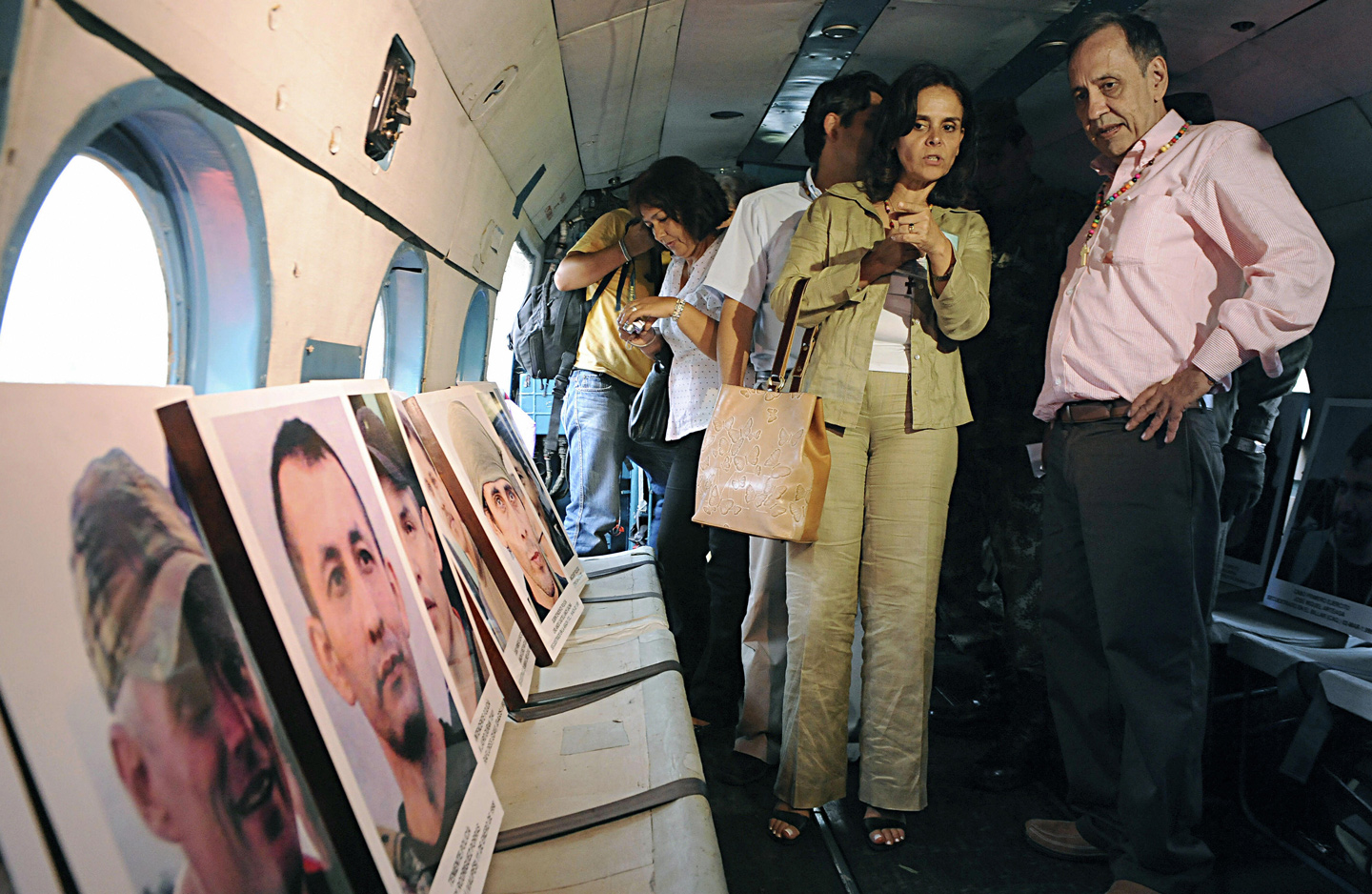 Former guerrilla hostage Oscar Tulio Lizcano (R) and his wife Martha look at pictures of the FARC hostages released during the Army's Jaque Operation, after thanking the soldiers of the third division of the National Army during a religious ceremony in Cali, department of Valle del Cauca, Colombia, on October 31, 2008. Former lawmaker Lizcano thanked the soldiers for helping him after he escape to freedom the past weekend, towed by his jailer, former guerrilla member Wilson Bueno Largo, aka 'Isaza', who deserted from the rebel ranks.  AFP PHOTO/Luis ROBAYO (Photo credit should read LUIS ROBAYO/AFP/Getty Images)