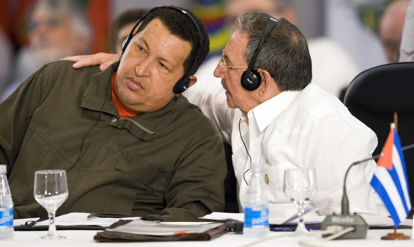 Cuba's President Raul Castro (R) whispers in Venezuela's President Hugo Chavez's ear during the South America and the Caribbean Summit in Sauipe, Brazil, on December 16, 2008. Latin American presidents gathered in northeastern Brazil for a summit dominated by concern over the accelerating global economic crisis. The two-day meeting of leaders of 33 Latin American and Caribbean nations -- including, for the first time, Cuban President Raul Castro -- comes as the region's governments grapple with slumping currencies, plummeting trade, shaved growth and climbing debt.  AFP PHOTO/Antonio Scorza (Photo credit should read ANTONIO SCORZA/AFP/Getty Images)