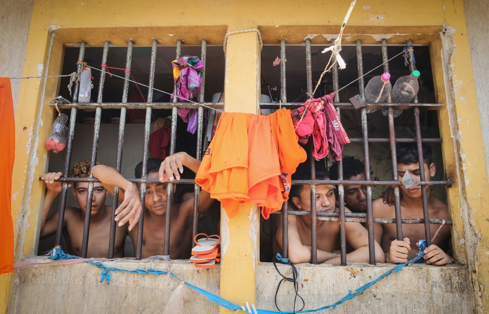 SAO LUIS, BRAZIL - JANUARY 27:  Inmates stand in their cell in the Pedrinhas Prison Complex, the largest penitentiary in Maranhao state, on January 27, 2015 in Sao Luis, Brazil. Previously one of the most violent prisons in Brazil, Pedrinhas has seen efforts from a new state administration, new prison officials and judiciary leaders from Maranhao which appear to have quelled some of the unrest within the complex. In 2013, nearly 60 inmates were killed within the complex, including three who were beheaded during rioting. Much of the violence stemmed from broken cells allowing inmates and gang rivals to mix in the patios and open spaces of the complex. Officials recently repaired and repopulated the cells allowing law enforcement access and decreasing violence among prisoners, according to officials. Other reforms include a policy of custody hearings and real-time camera feeds. According to officials there have been no prisoner on prisoner killings inside the complex in nearly four months. Critics believe overcrowding is one of the primary causes of rioting and violence in Brazil's prisons. Additionally, overcrowding has strengthened prison gangs which now span the country and contol certain peripheries of cities including Rio de Janeiro, Sao Paulo and Sao Luis. Brazil now has the fourth-largest prison population in the world behind the U.S., Russia and China. The population of those imprisoned had quadrupled in the past twenty years to around 550,000 and the country needs at least 200,000 new incarceration spaces to eliminate overcrowding. A vast increase in minor drug arrests, a dearth of legal advice for prisoners and a lack of political will for new prisons have contributed to the increases.  (Photo by Mario Tama/Getty Images)