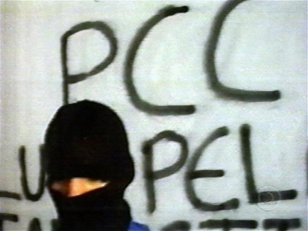 Sao Paulo, BRAZIL:  This TV grab is part of the video exhibited by Globo TV network in last sunday early morning as an imposition to free Brazilian TV reporter Guilherme Portanova, in Sao Paulo, Brazil. Portanova was set free by the Primeiro Comando de la Capital (PCC) gang after his television network on Sunday met the kidnappers' demands by broadcasting a three-and-a-half minute videotape they made. In the videotape, a hooded man representing the much-feared criminal group -- whose name in English means First Capital Command -- criticizes Brazil's penal system and demands better conditions in Sao Paolo's prisons. Portanova, who was freed early Monday from the trunk of a car parked near TV Globo's Sao Paolo offices, said he was treated well by his captors.   AFP PHOTO  (Photo credit should read -/AFP/Getty Images)