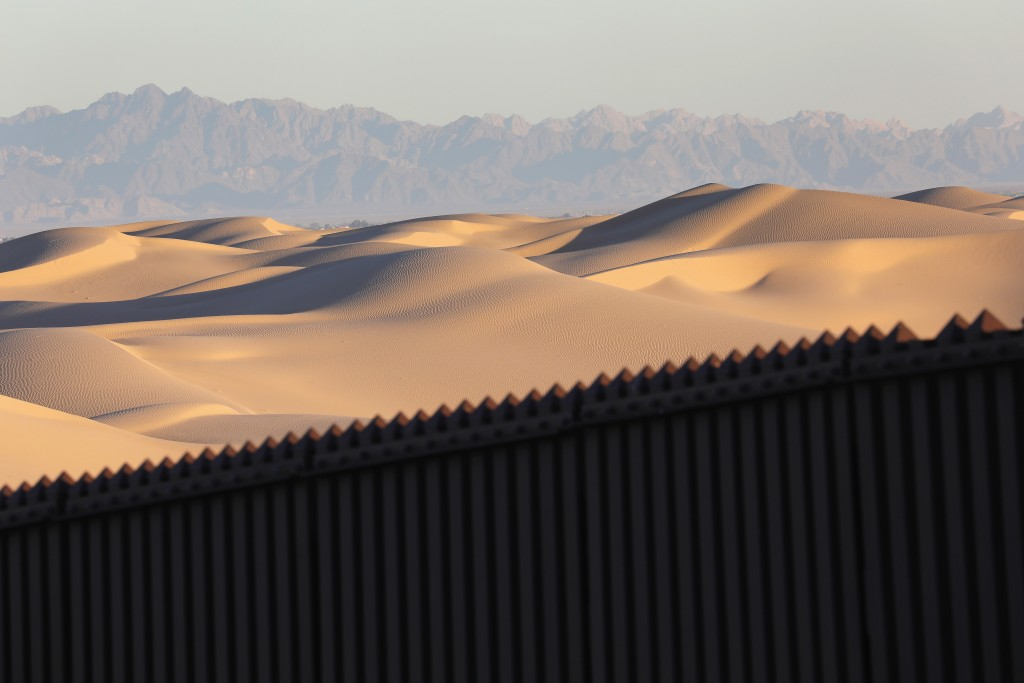 """FELICITY, CA - NOVEMBER 17: Mexico is seen over the U.S.-Mexico border fence at the Imperial Sand Dunes on November 17, 2016 near Felicity, California. The 15-foot border fence there, also known as the """"floating fence,"""" sits atop the dunes and moves with the shifting sands. Border Patrol agents say they catch groups of illegal immigrants and drug smugglers crossing in from Mexico there daily, despite the forbidding terrain.  (Photo by John Moore/Getty Images)"""