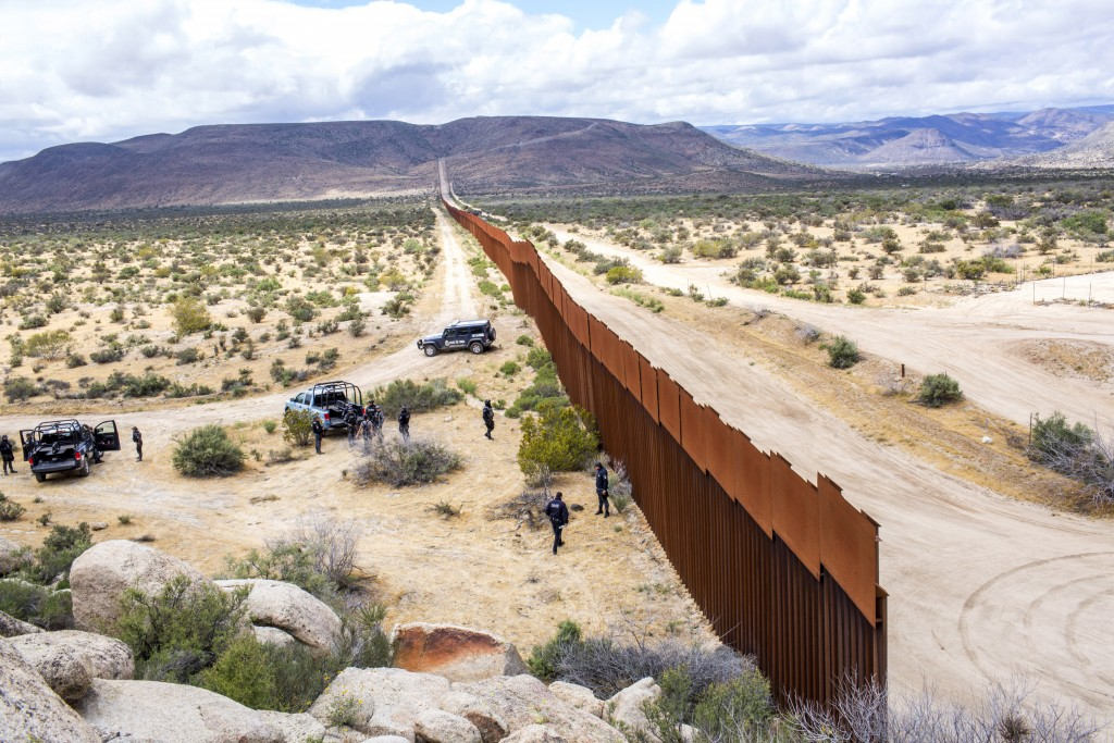 TIJUANA, MX. - APRIL 8 2016: Mexican Federal Policeman escort a tour of the border wall near Tijuana. Natalie Keyssar
