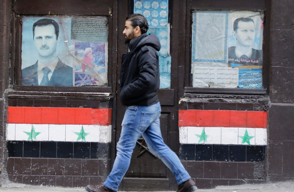 TOPSHOT - A Syrian man walks past posters of Syrian President Bashar al-Assad on a shop front in the capital Damascus on January 3, 2017. / AFP / LOUAI BESHARA        (Photo credit should read LOUAI BESHARA/AFP/Getty Images)