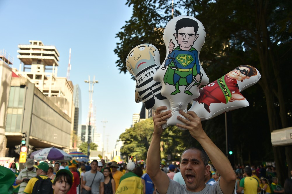 A mand holds balloons depicting (L-R) Brazilian former President Luiz Inacio Lula Da Silva, Brazilian Judge Sergio Moro and Brazilian President Dilma Rousseff during a demo in support of Rousseff's impeachment in Sao Paulo, Brazil on April 17, 2016. Rousseff risks being driven from office if the lower house votes in favor of an impeachment trial Sunday in Brasilia. / AFP / NELSON ALMEIDA        (Photo credit should read NELSON ALMEIDA/AFP/Getty Images)