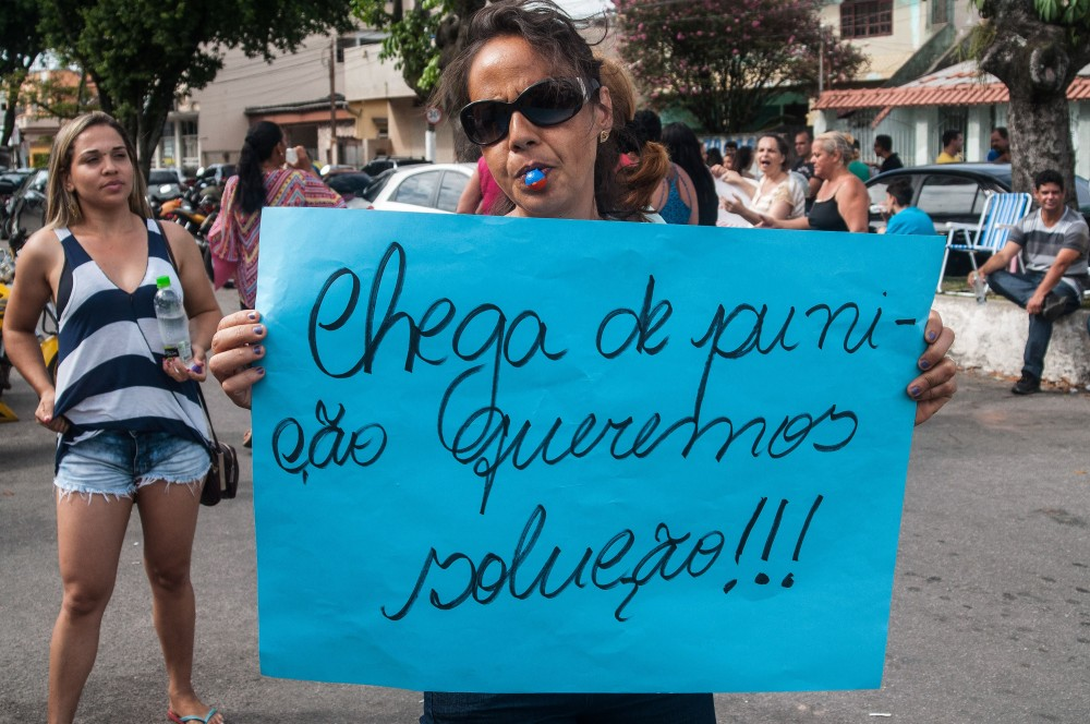 """A relative of a military police shows a sign reading """"Enough of punishment, we want solutions!"""" during a protest in support of a police strike at the entrance of a police station in Vila Velha, near Vitoria, in eastern Brazil on February 6, 2017.<br /><br /><br /><br /><br /><br /><br /><br /><br /><br /><br /><br /><br /><br /><br /><br /><br /><br /><br /><br /><br /><br /><br /><br /><br /><br /><br /><br /> Brazil's government authorized deployment of troops Monday to the coastal city of Vitoria, which has been left at the mercy of criminals following a police strike.<br /><br /><br /><br /><br /><br /><br /><br /><br /><br /><br /><br /><br /><br /><br /><br /><br /><br /><br /><br /><br /><br /><br /><br /><br /><br /><br /><br /> / AFP / Vinicius Moraes (Photo credit should read VINICIUS MORAES/AFP/Getty Images)"""