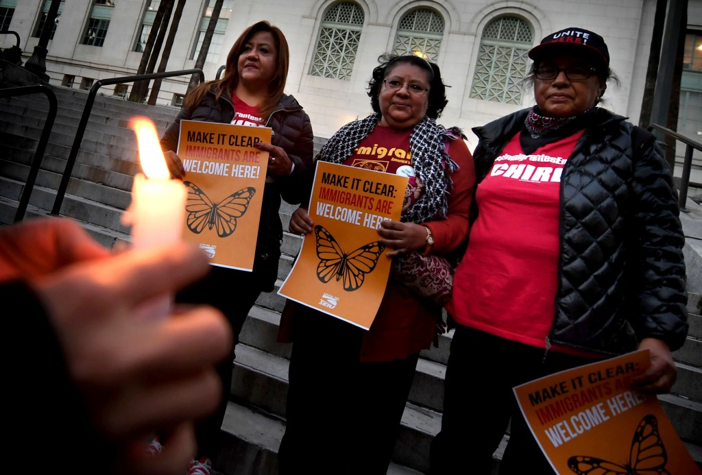 """Migrant rights groups look on during a vigil to protest against US President Donald Trump's new crackdown on """"sanctuary cities"""", outside the City Hall in Los Angeles on January 25, 2017.Some 300 such cities, counties or states -- from New York to Los Angeles -- exist throughout the United States, and many of them have vowed since Trump's election to protect the estimated 11 million undocumented migrants living in the country. / AFP / Mark RALSTON (Photo credit should read MARK RALSTON/AFP/Getty Images)"""