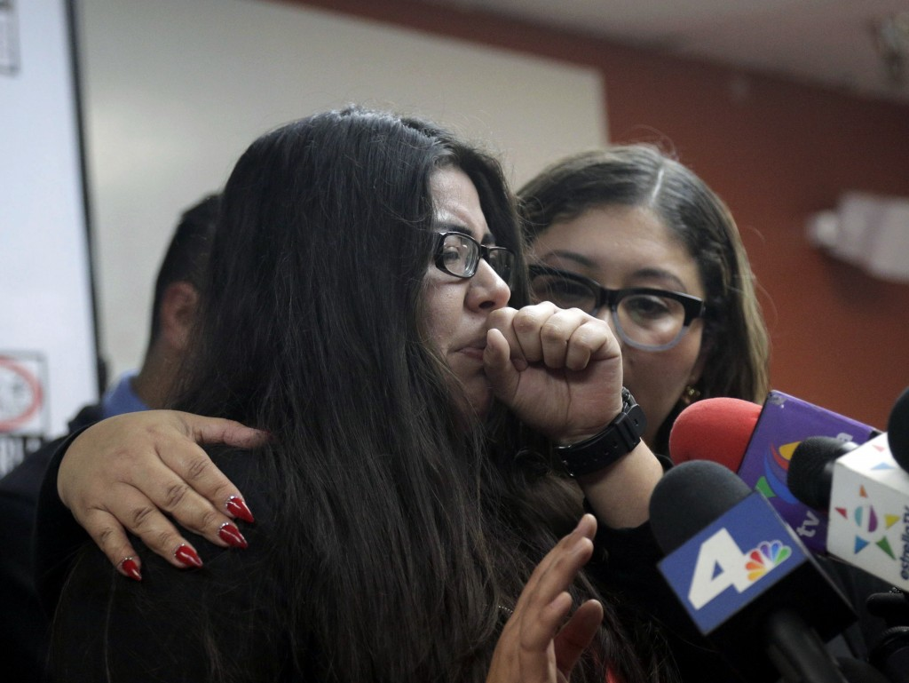 CLARIFIES THAT FATHER HAS NOT BEEN DEPORTED- Marlene Mosqueda, left, who's father was arrested by ICE early Friday morning to be deported, is comforted at a news conference by her attorney Karla Navarrette at The Coalition for Humane Immigrant Rights of Los Angeles (CHIRLA) on Friday, Feb. 10, 2017. Navarrete, said she sought to stop Mosqueda from being placed on a bus to Mexico and was told by ICE that things had changed. She said another lawyer filed federal court papers to halt his removal. (AP Photo/Nick Ut)